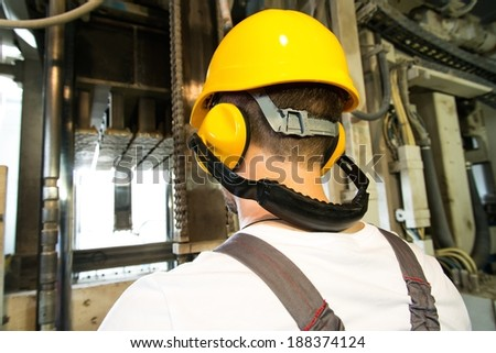 Worker in safety hat and headphones working behind machine on a factory - stock photo