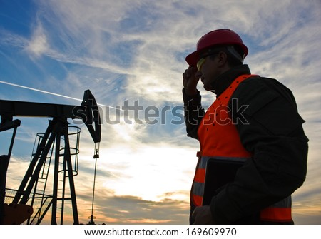 worker in the oil field industry at dusk,image soft focus,  best focus on the worker - stock photo