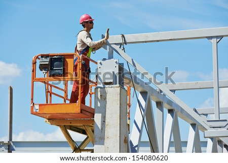 worker in uniform and safety protective equipment at metal construction frames installation and assemblage - stock photo