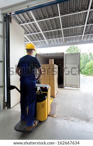 Worker in uniform on a fork lift - stock photo