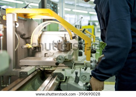 Worker in uniform operating in manual lathe. Mechanical technician measuring cutting tool before cnc milling machine center at tool workshop. - stock photo