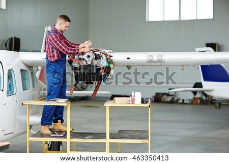 Worker in uniform repairing jet engine