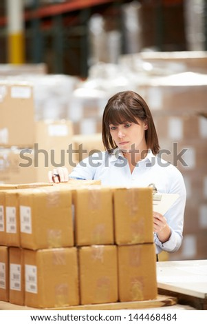 Worker In Warehouse Preparing Goods For Dispatch - stock photo