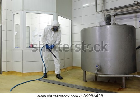 worker in white protective uniform,mask,gloves  with high pressure washer at  large industrial process tank  cleaning floor  in plant - stock photo