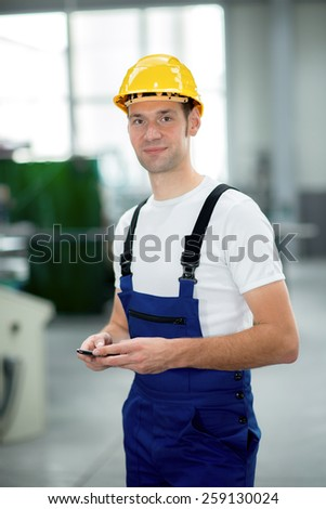 worker in work clothes with yellow helmet in factory