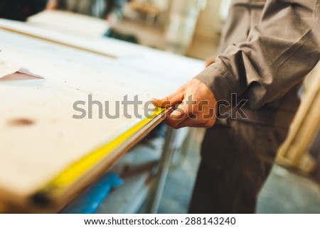 Worker in work wear measures chip wood with long yellow ruler on a workbench. Selective focus on hand - stock photo