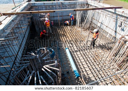 worker in workwear making reinforcement metal framework for concrete pouring.