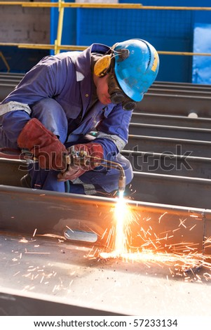 worker inside factory cut metal using blowtorch - stock photo