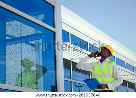 Worker inspector  in hardhat  calling on cellphone near modern building