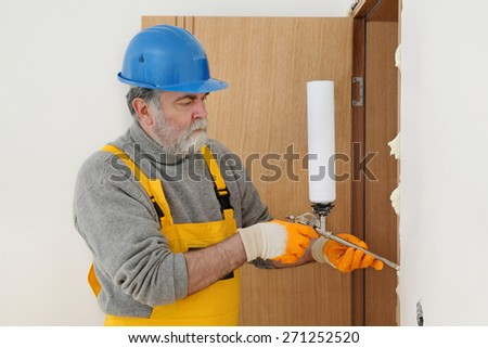 Worker install door, using polyurethane foam to fix it at wall - stock photo