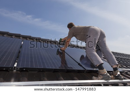 worker installing alternative energy photovoltaic solar panels.
