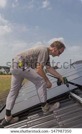 worker installing alternative energy photovoltaic solar panels on the roof of a single family house