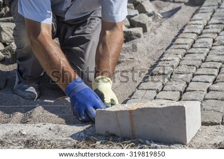 Worker installing granite cubes for pathway. Laying natural granite stone cobbles in sand. Natural stone paving. Shallow DOF. - stock photo