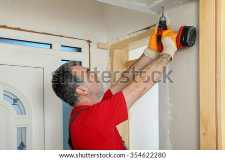 Worker installing gypsum board, using electric drill or screwdriver, home renovation