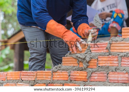 Worker installing red brick for construction site - stock photo