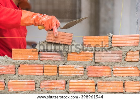 Worker installing red brick for construction site