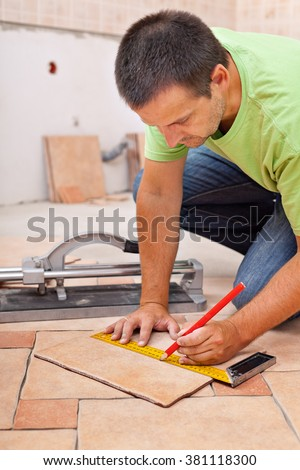 Worker installs ceramic tiles - marking them for cutting - stock photo