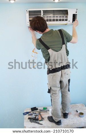 Worker installs grid on the air conditioner in the new apartment, view from the back - stock photo