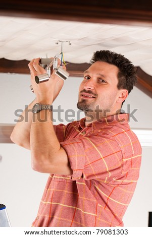 Worker is installing a luster on the ceiling - stock photo