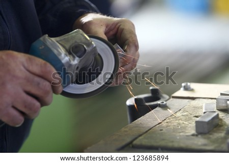 Worker is shaping a metal part in a factory with a grinder - stock photo