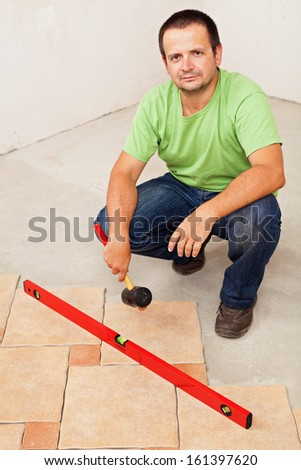 Worker laying ceramic floor tiles crouching and holding a rubber hammer - stock photo