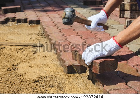 worker laying red concrete paving blocks. - stock photo