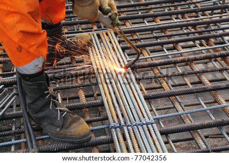 Worker legs in orange clothes weld metal grating by acetylene torch - stock photo
