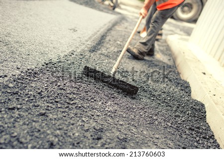 Worker leveling fresh asphalt on a road construction site, industrial buildings and teamwork. Vintage effect