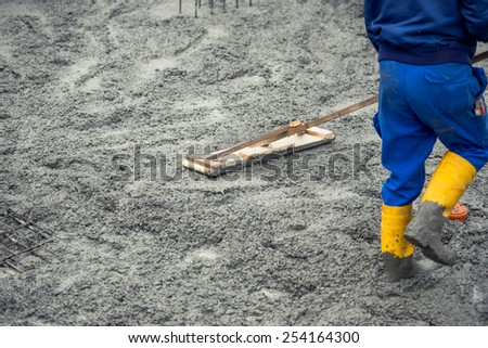 Worker leveling with wooden trowel the fresh poured concrete or cement at construction site - stock photo
