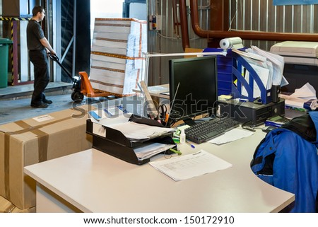 Worker loading boxes on forklift  in the new  modern warehouse. In the foreground workplace with documents - stock photo