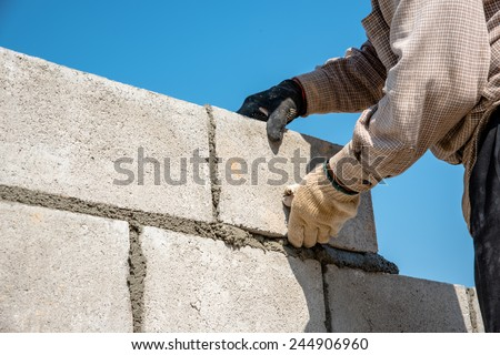 worker make concrete wall by cement block and plaster at construction site ,worker hand wearing glove laying block to making wall - stock photo