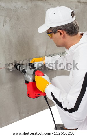 Worker making a hole through a lath - stock photo
