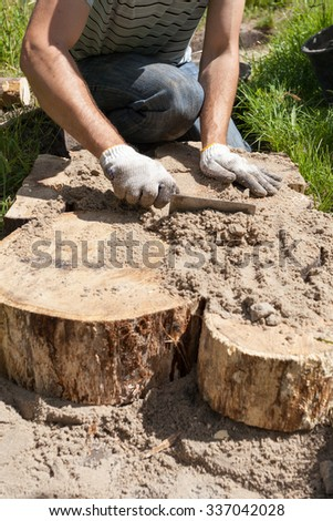 Worker making a walk path in garden decorated with wooden stumps