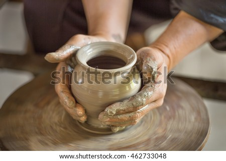 Worker making clay pot on pottery wheel