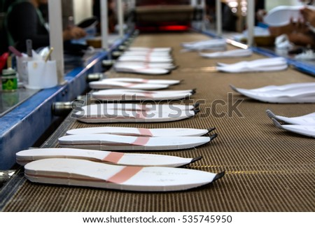 worker making shoe sole component part in production line of footwear industry