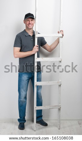 Worker man hold a ladder - stock photo