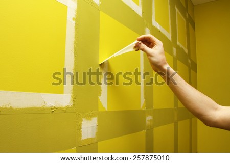 worker man removing masking tape from painting wall - stock photo