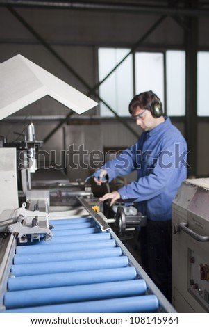 worker measuring a piece at machine in factory - stock photo