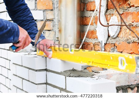 Worker measuring anger with level. chimney installation