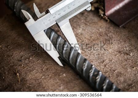 Worker measuring Deformed bars steel with Vernier Caliper - stock photo