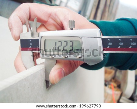 Worker Measuring the Level of Gypsum Board Thickness for Quality Assurance