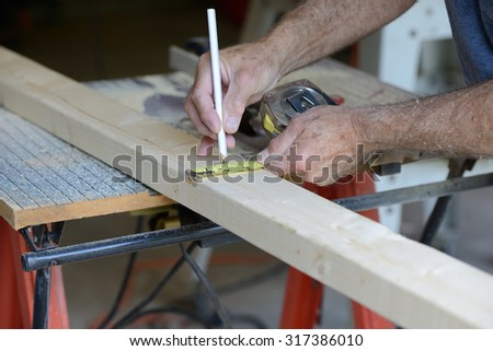 Worker Measuring Wood to Cut on Table Saw - stock photo