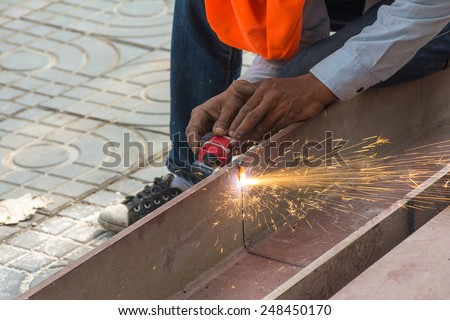 worker Metal Cutting large steel with Plasma cutters. Workman is working by use Plasma cutters the iron in building. Spark splash around the ground. - stock photo
