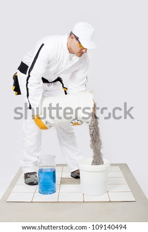 Worker mix tile adhesive bucket  of water white tiles - stock photo