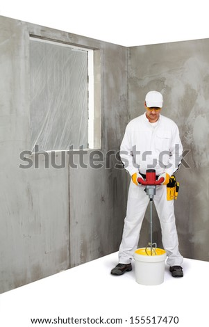 Worker mixing a plaster with a stirrer machine - stock photo