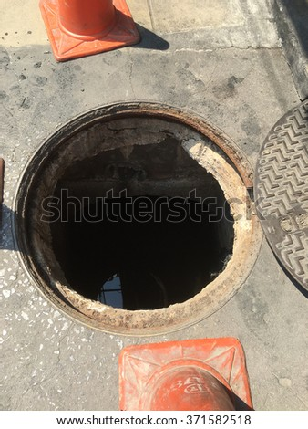 worker moves the manhole cover to cleaning for clogs - stock photo