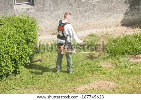 Worker mowing the grass with trimmer