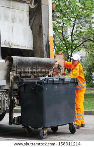 Worker of recycling garbage collector truck loading waste and trash bin - stock photo