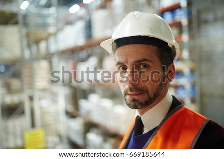 Worker of storehouse distribution looking at camera