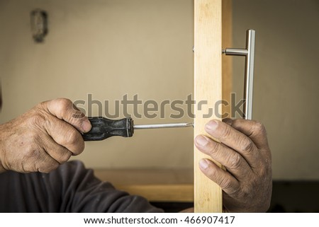 Worker of the construction arming a wood closet
